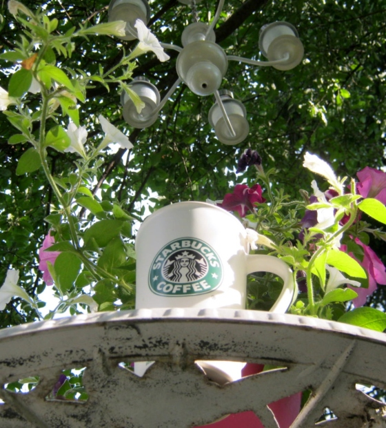 Sky through table, cup, chandelier and crabapple tree.
